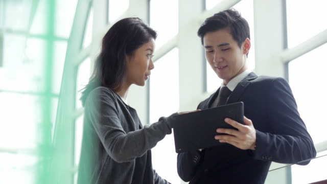 ms couple working together on digital tablet in an office. - 絆点の映像素材/bロール