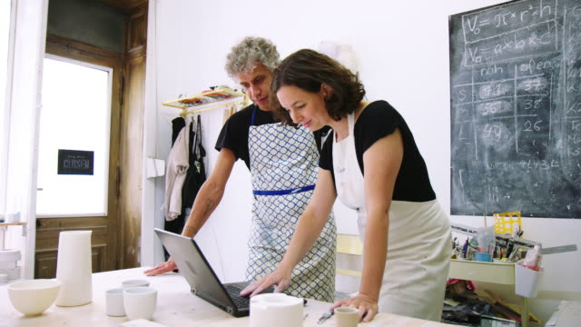 couple working together on laptop at a ceramic workshop - mid adult couple stock videos & royalty-free footage