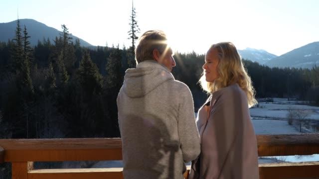 vidéos et rushes de couple wrap themselves in blanket, on deck overlooking mountains - 55 59 ans