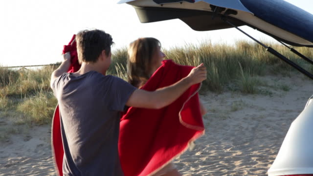 TS couple wrapped in blanket run on beach towards sea/Tarifa/Andalucia/Spain