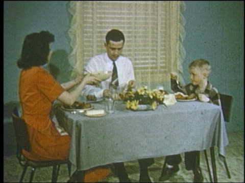 1952 couple + young son sitting at dinner table / mother passing bowl - two parents stock videos & royalty-free footage