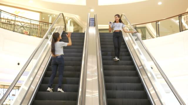 couple young woman using smartphone on escalator