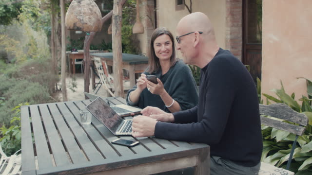 couple/co workers talking/looking at laptop - arbeitszimmer stock-videos und b-roll-filmmaterial