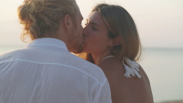 couples age 25-29 yearold of latin american and hispanic ethnicity kissing with romance along edge of sunset sea on sand beach. happy family holidays. non-caucasian honeymoon concept. - wonderlust stock videos & royalty-free footage