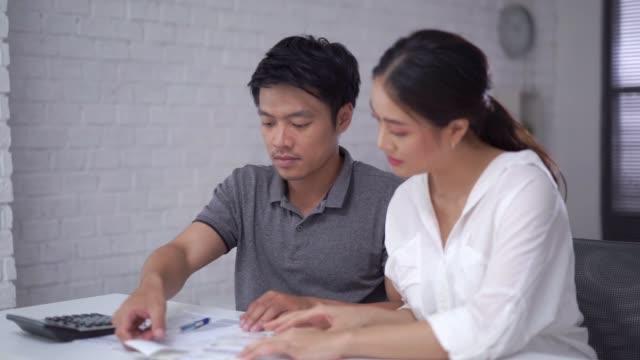 vídeos y material grabado en eventos de stock de las parejas están calculando gastos y facturas - cinta para caja registradora
