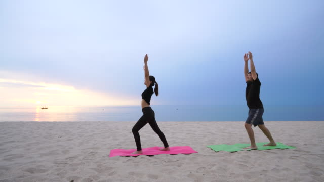 couples are playing yoga on the beach - wellbeing stock videos & royalty-free footage