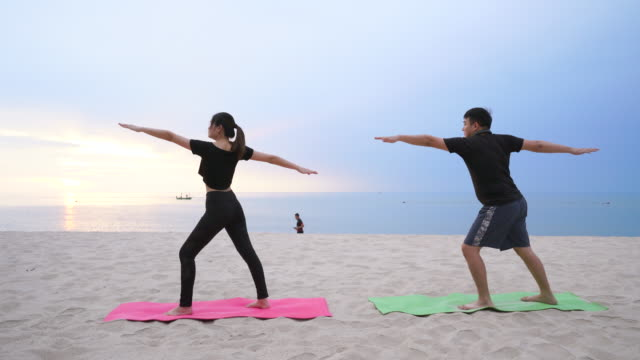 couples are playing yoga on the beach - zen like stock videos & royalty-free footage