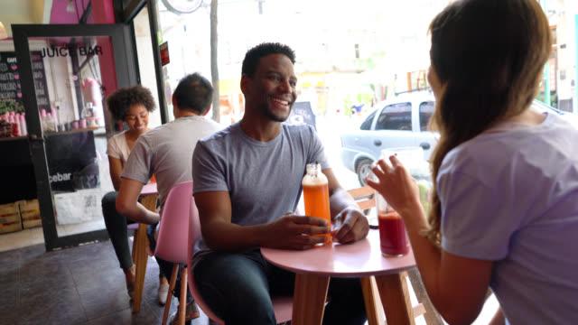 Couples at a juice bar talking and enjoying a healthy juice