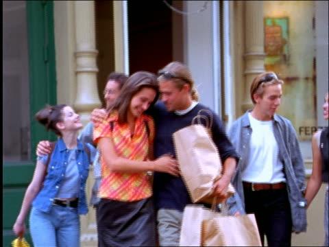 3 couples carrying shopping bags walking on nyc street - 1990~1999年点の映像素材/bロール