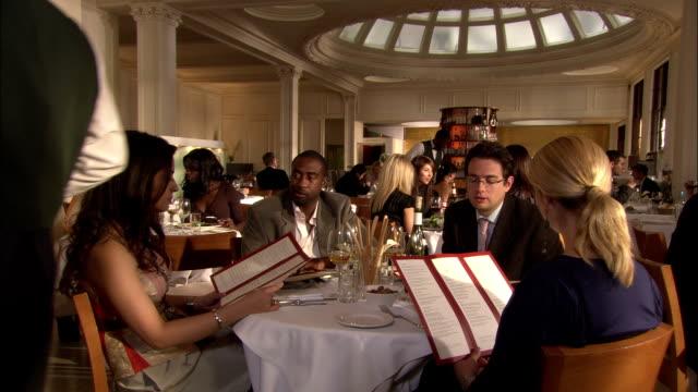 vídeos de stock e filmes b-roll de couples chat while on a double date. - sala de jantar