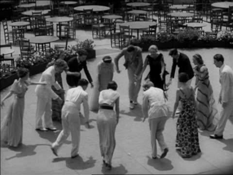 "B/W 1937 HA couples dancing ""Big Apple"" in circle outdoors + raising arms overhead / Washington, DC / newsreel"