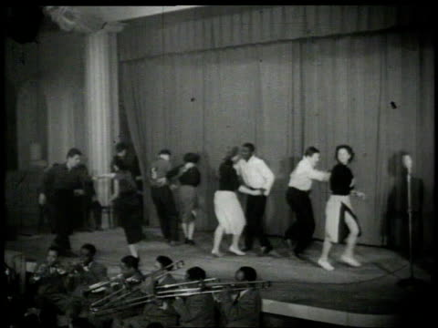 1926 montage couples dancing the lindy hop on stage - 1926 stock-videos und b-roll-filmmaterial