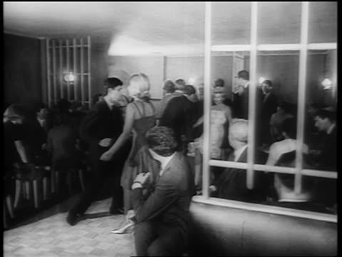 B/W 1961 couples dancing the Twist on dance floor at party / newsreel