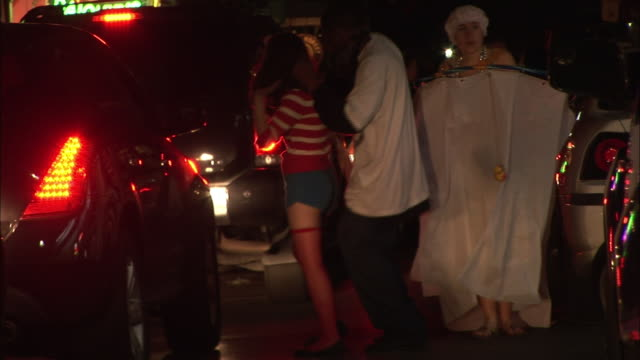 Couples dressed in Halloween costumes dance in a street.