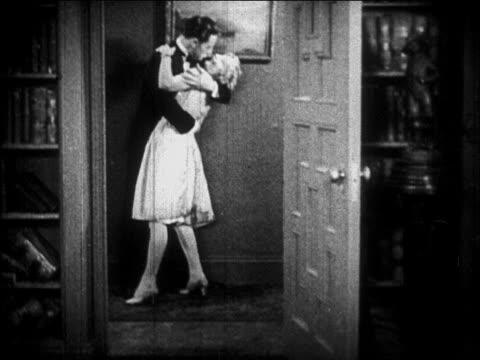 B/W 1926 couples embracing + kissing in doorway / newsreel