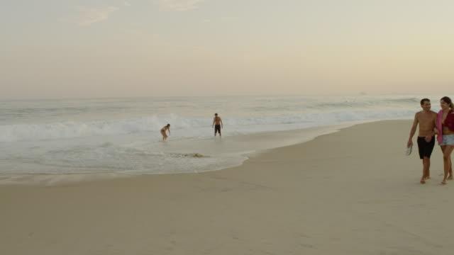 vídeos de stock, filmes e b-roll de rio de janeiro-june 16: couples enjoy dusk at ipanema beach on june 16, 2013 in rio de janeiro. - short curto