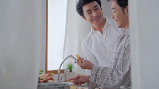 vídeos de stock, filmes e b-roll de casais gay romântico pela manhã. casais felizes gays fazendo um pequeno-almoço na cozinha. casal gay masculino, preparando uma refeição juntos na cozinha. conceito lgbt. lgbtq casa vida - happy meal