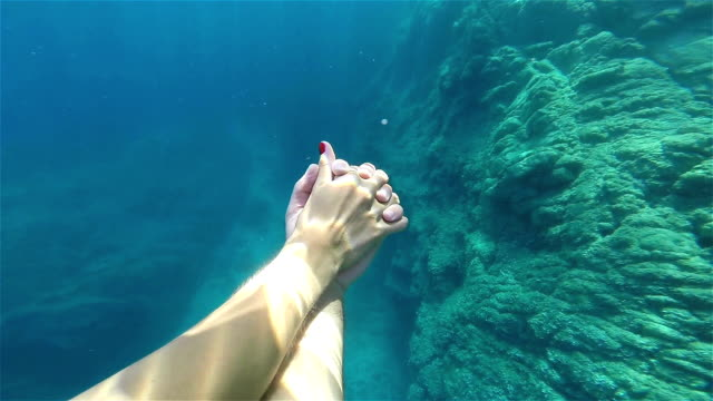Couple's hands underwater