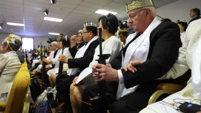 couples hold ar15 rifles and other guns during a ceremony at the world peace and unification sanctuary on february 28 2018 in newfoundland... - congregation stock videos and b-roll footage