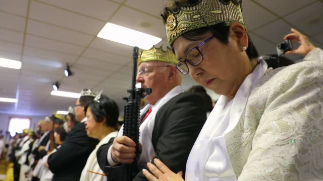 couples hold ar15 rifles and other guns during a ceremony at the world peace and unification sanctuary on february 28 2018 in newfoundland... - frieden stock-videos und b-roll-filmmaterial