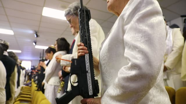 Couples hold AR15 rifles and other guns during a ceremony at the World Peace and Unification Sanctuary on February 28 2018 in Newfoundland...
