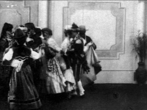 b/w 1903 couples in costumes dancing at masquerade ball - 1903 stock-videos und b-roll-filmmaterial