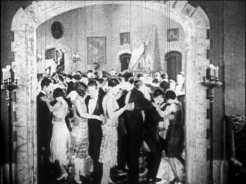 B/W 1926 couples in formalwear dancing Charleston at party inside doorway / newsreel