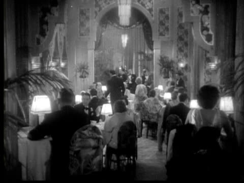 stockvideo's en b-roll-footage met 1931 b/w montage couples in formalwear having dinner at nightclub/ los angeles, california, usa/ audio - 1930