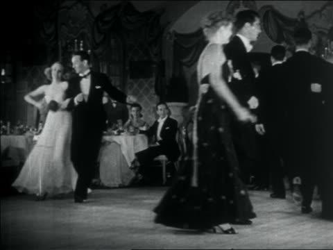 vídeos de stock, filmes e b-roll de b/w 1938 couples in formalwear strolling + dancing at elegant nightclub / nyc / documentary - 1930