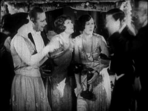 b/w 1926 couples in formalwear waving arms + singing at party / newsreel - 1926 stock videos & royalty-free footage