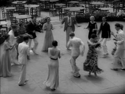 """B/W 1937 HA couples in summer outfits dancing """"Big Apple"""" in circle outdoors / Washington, DC / newsreel"""