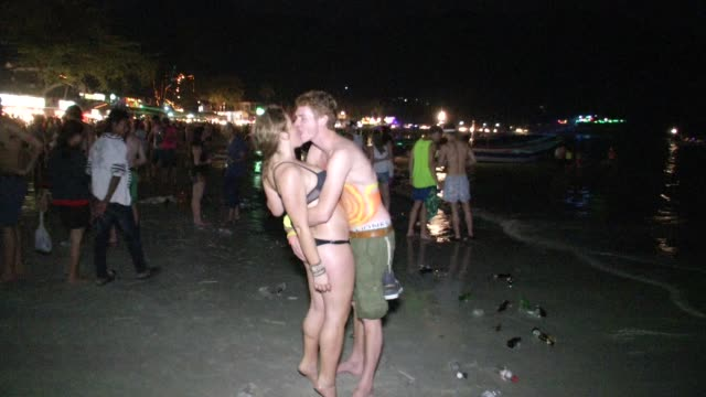 couples kiss on the beach during the full moon party on ko phangan in thailand on jan 4 2015 - ko phangan stock videos and b-roll footage