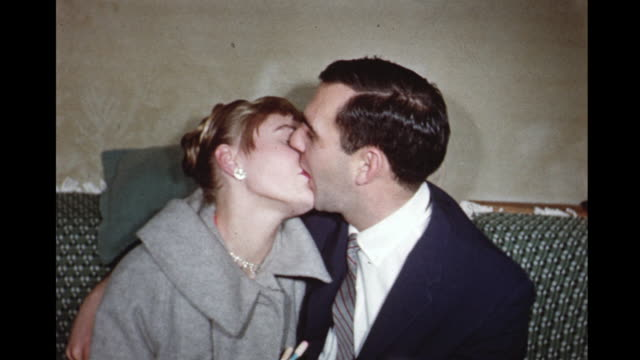 1958 home movie couples kissing on sofa on new years eve / toronto, canada - geschichtlich stock-videos und b-roll-filmmaterial