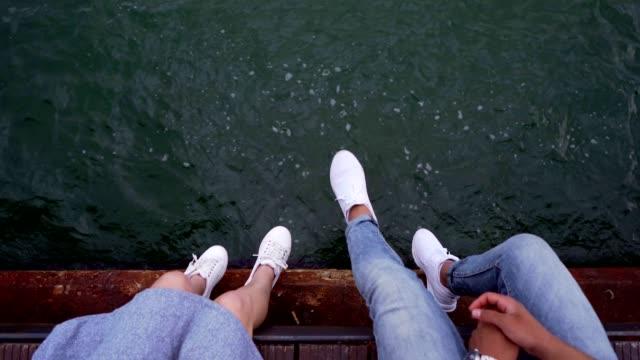 一對夫婦的腿從碼頭上晃來晃去 - 懸掛的 個影片檔及 b 捲影像