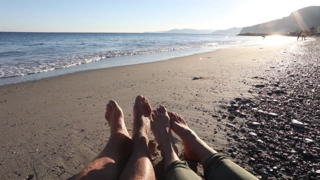 couple's legs relaxing on beach, surf behind - barefoot stock videos & royalty-free footage