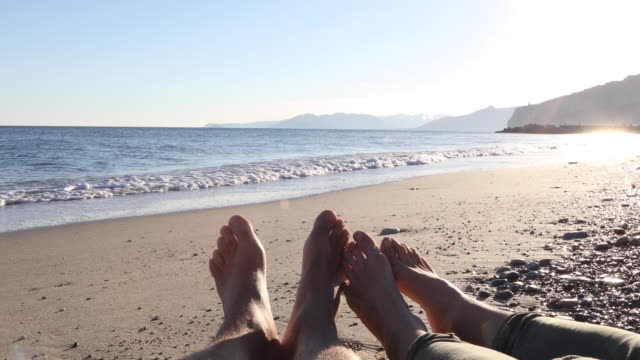 couple's legs relaxing on beach, surf behind - human limb stock videos & royalty-free footage