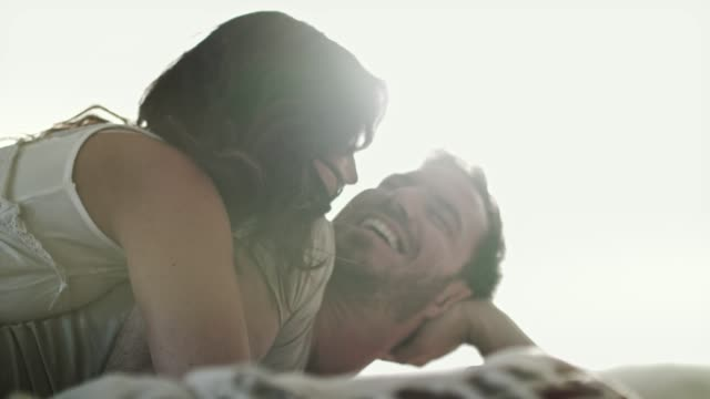 couple's morning routine of cuddling and laughter together in bed - mid adult couple stock videos & royalty-free footage