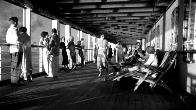 couples relax at the ocean-liner rail or in deck chairs on an ocean liner in 1935. - 1935 stock videos & royalty-free footage