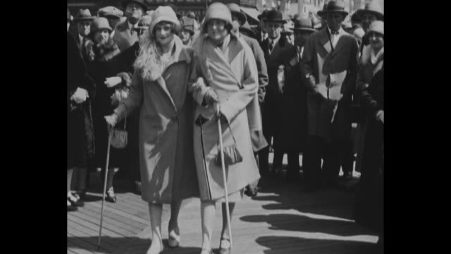 couples stroll down atlantic city boardwalk and ride in rolling chairs for easter parade / two women stroll arminarm in fancy coats and hats and with... - 1920 stock videos & royalty-free footage