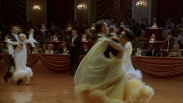 Couples twirl across a ballroom during a competition.