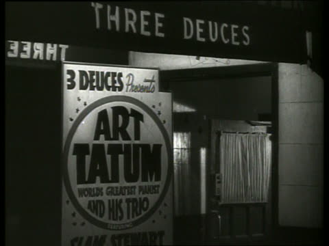 b/w couples walk into nightclub with art tatum poster - music poster stock videos & royalty-free footage