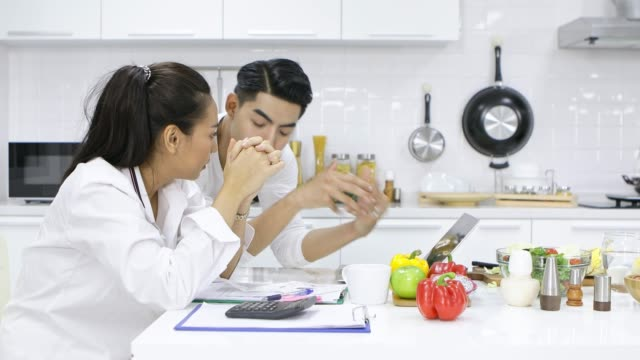 Couples with debt problems are discussing in the kitchen.