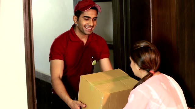 courier delivering a package to man, delhi, india - delivery person stock videos & royalty-free footage