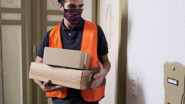 courier delivering the ordered products home during pandemic - building entrance stock videos & royalty-free footage