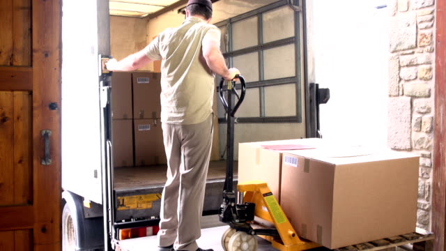 Courier / Delivery man loading Pallet into Truck