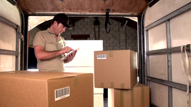 courier / delivery man on digital tablet in delivery truck - package stock videos and b-roll footage