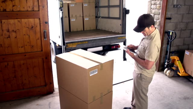 Courier / Delivery man on Digital Tablet in Warehouse