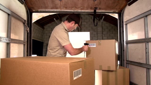 Courier / Delivery person scanning barcode on parcel in Delivery Truck