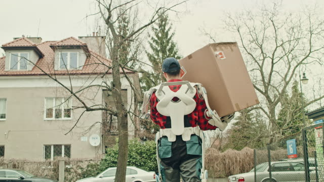 courier in powered exoskeleton is delivering package. - exoskeleton stock videos & royalty-free footage