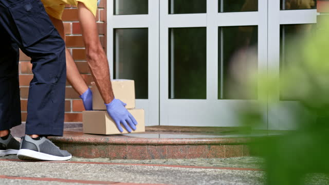 courier leaving the packages on the doorstep of a family home - doorstep stock videos & royalty-free footage